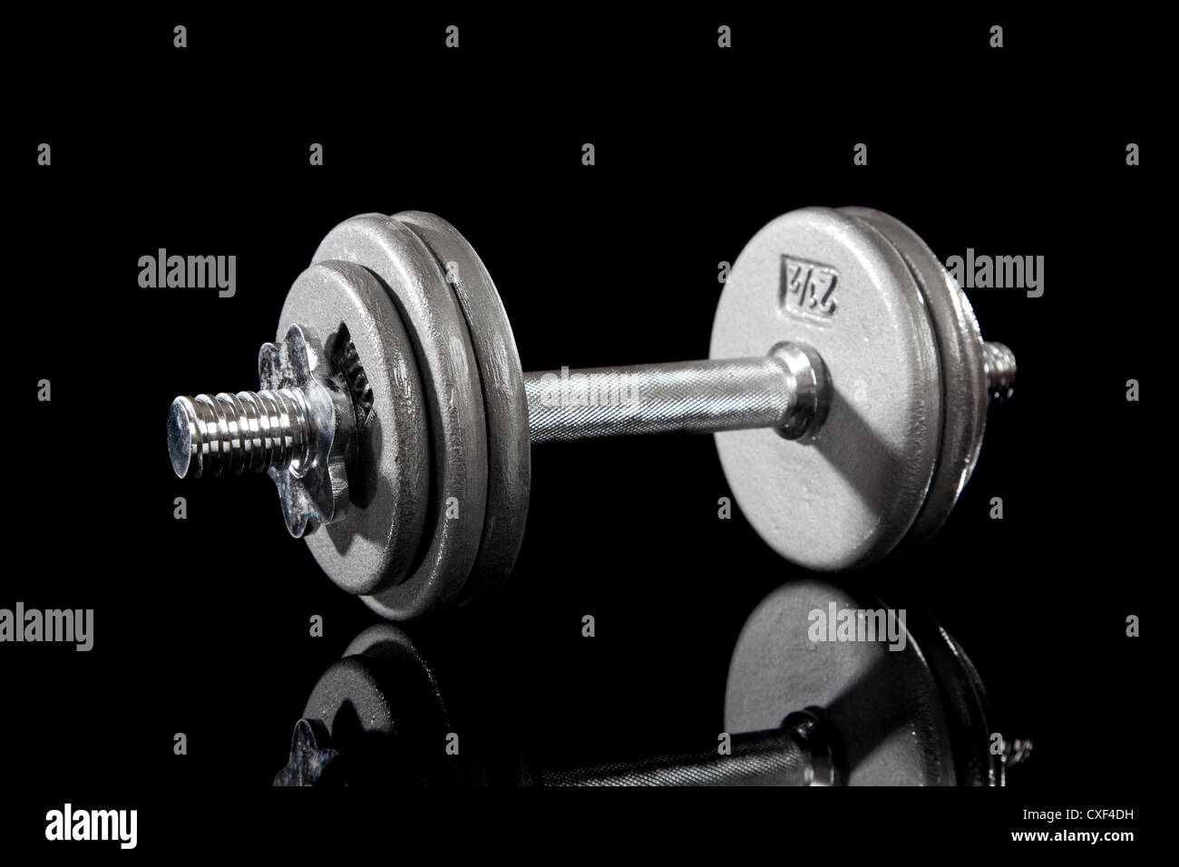 Dumbbell on a black background - Stock Image