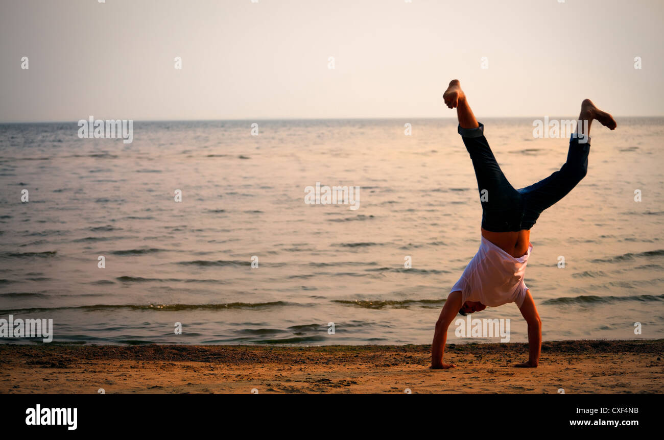 man doing handstand on beach - Stock Image
