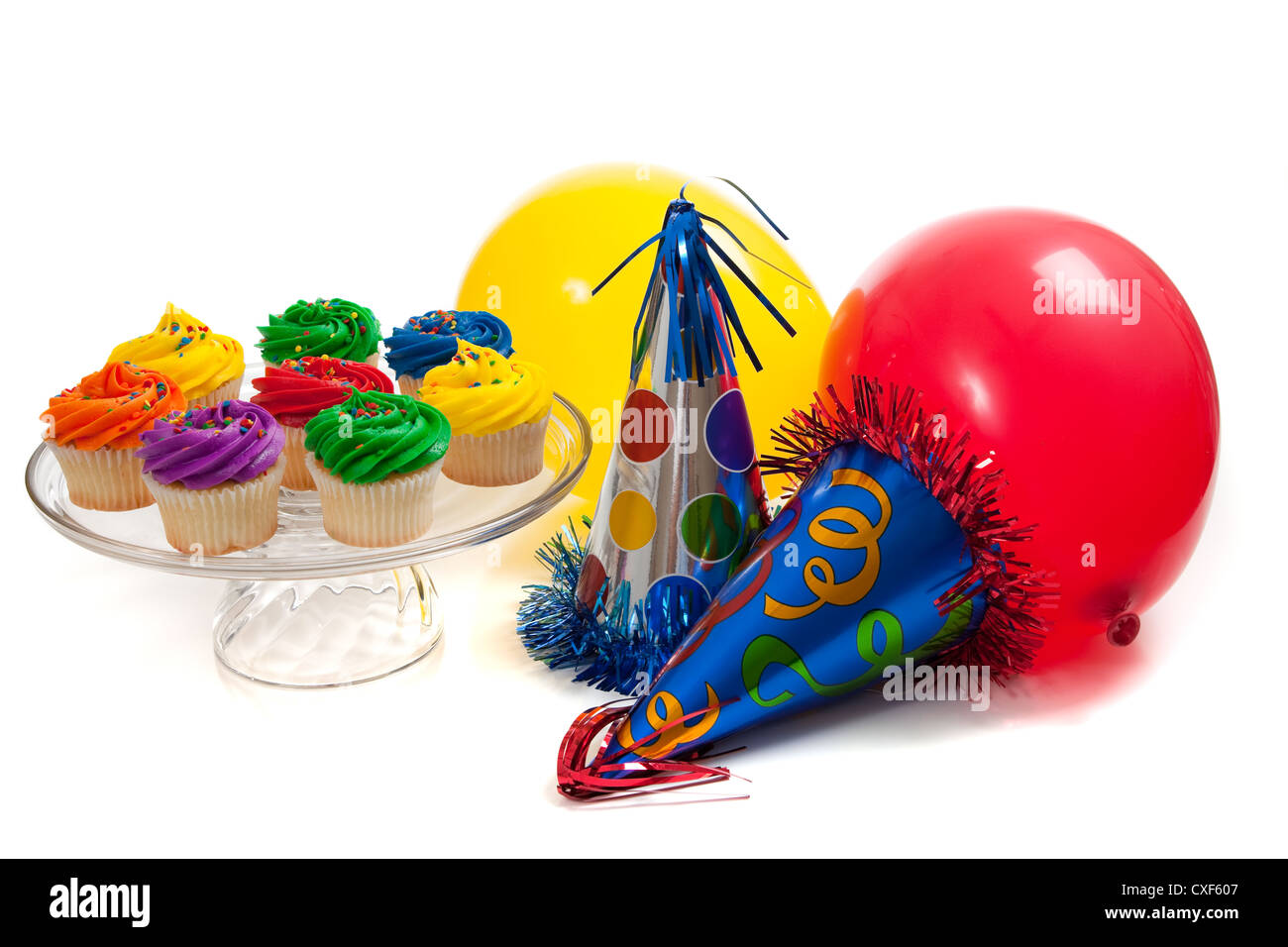 Brightly colored frosted cupcakes with birthday hats and balloons in the background - Stock Image