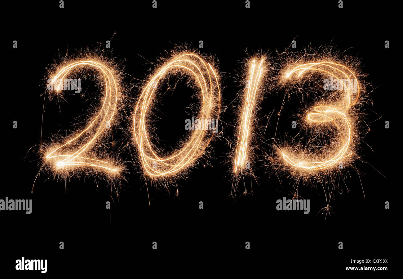 Number 2013 written with real sparklers on black background. - Stock Image