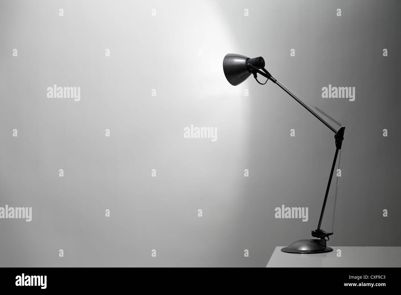 A Grey desk lamp pointed at a grey wall. - Stock Image