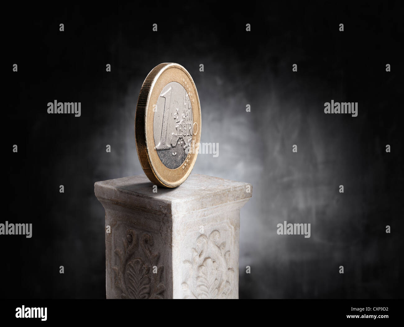 Euro coin on top of a plaster column. - Stock Image