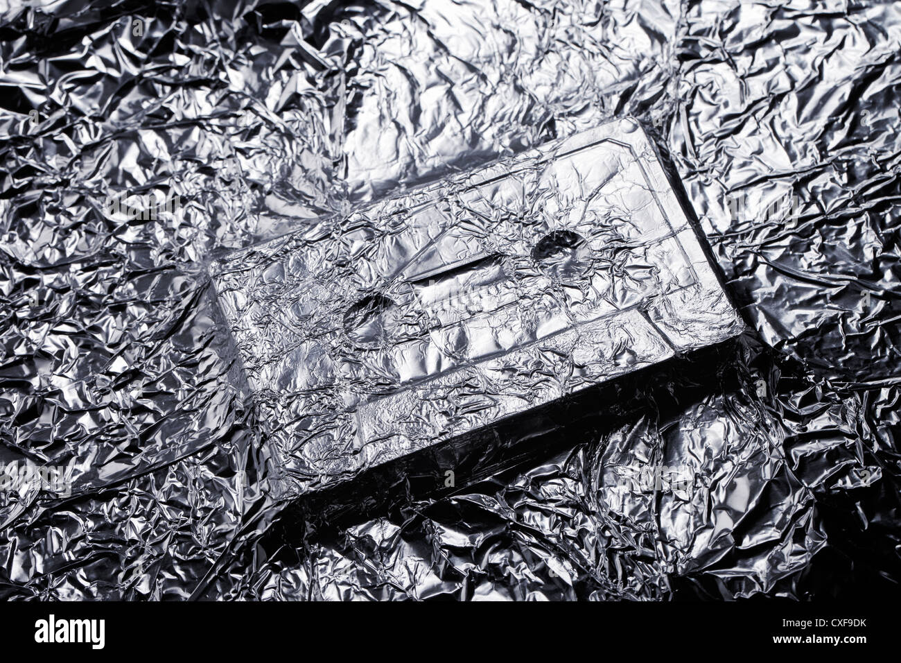 Audio compact cassette covered with aluminium foil. - Stock Image