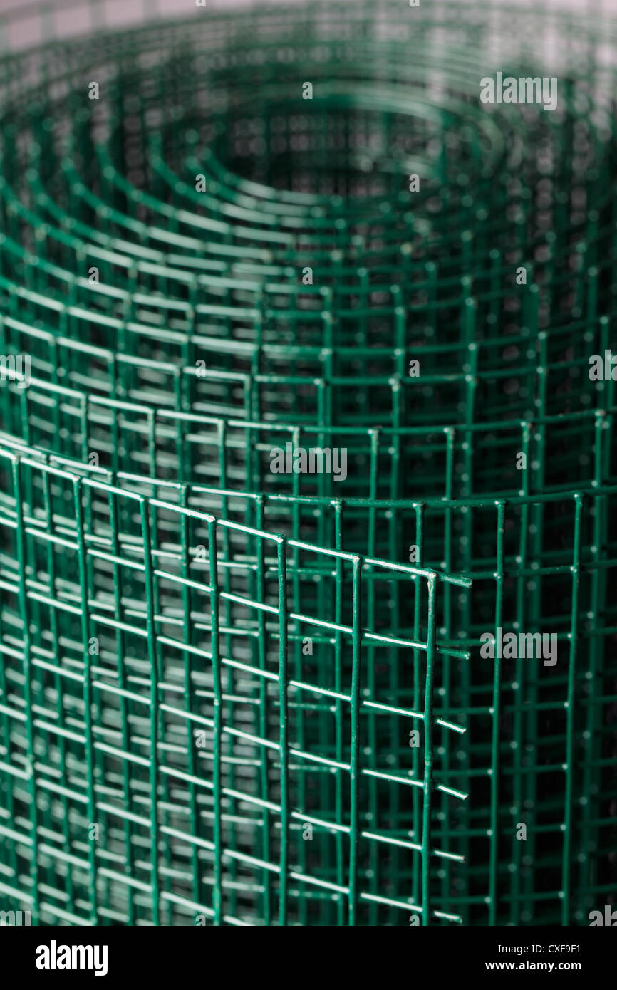Coated green metallic wire mesh used in gardening by protecting plants from animals. - Stock Image