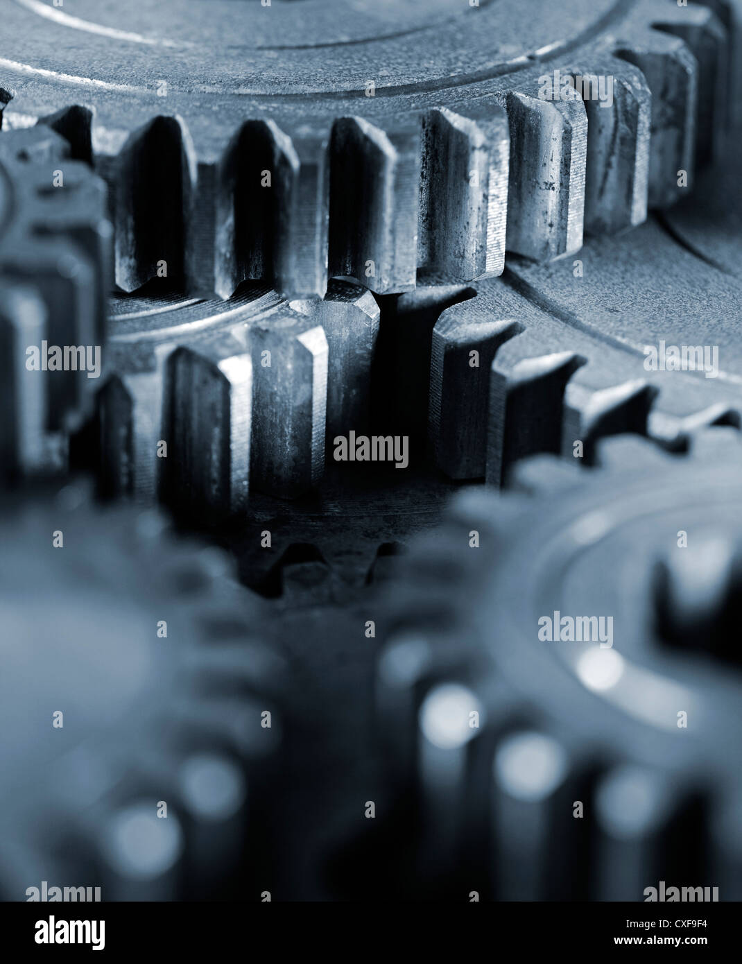 Blue tinted monochrome image of old cog gears. Very short depth-of-field. - Stock Image
