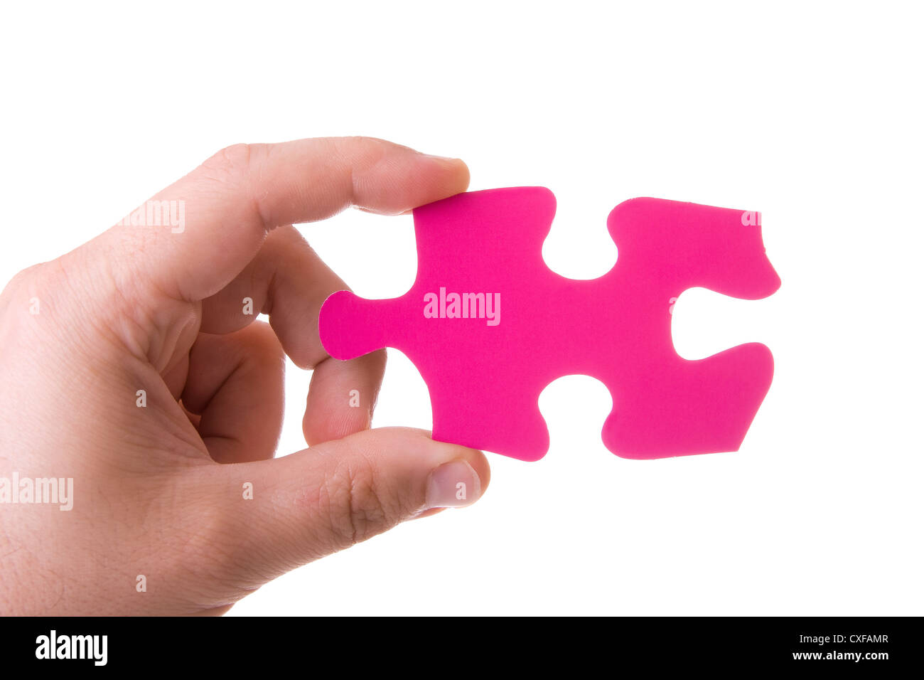 Hand holding a pink puzzle isolated on white - Stock Image