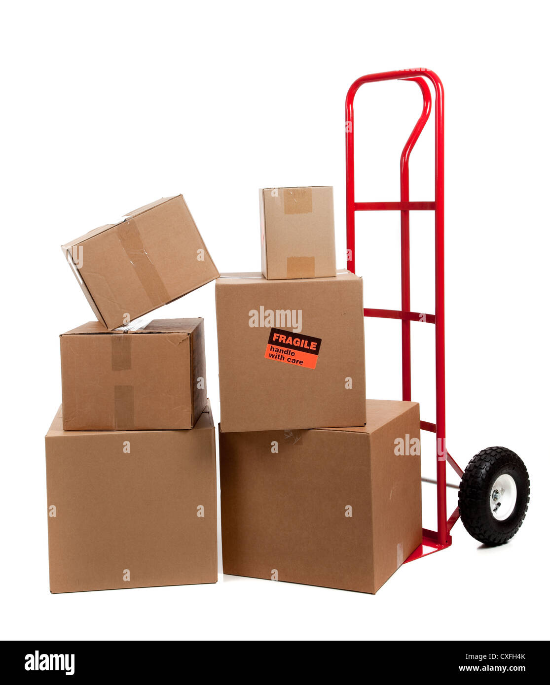 Stacks of cardboard boxes on a red hand truck - Stock Image