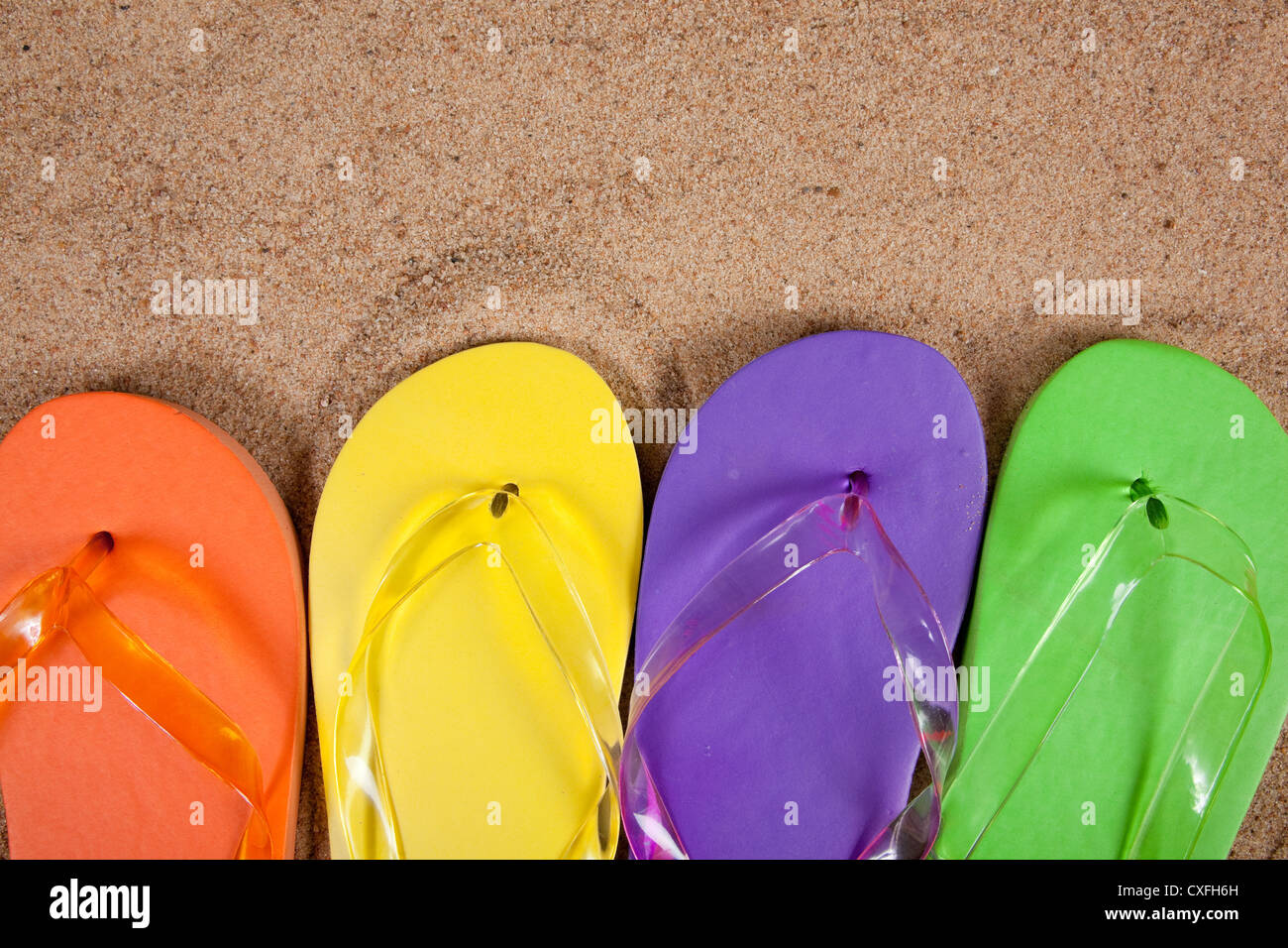 Row of carious colored flipflops on a sandy beach with copy space - Stock Image