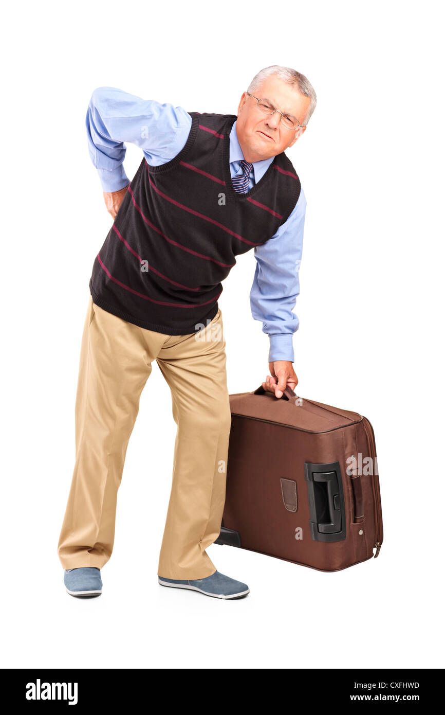 Full length portrait of a senior man lifting his luggage and suffering from a back pain isolated on white background - Stock Image