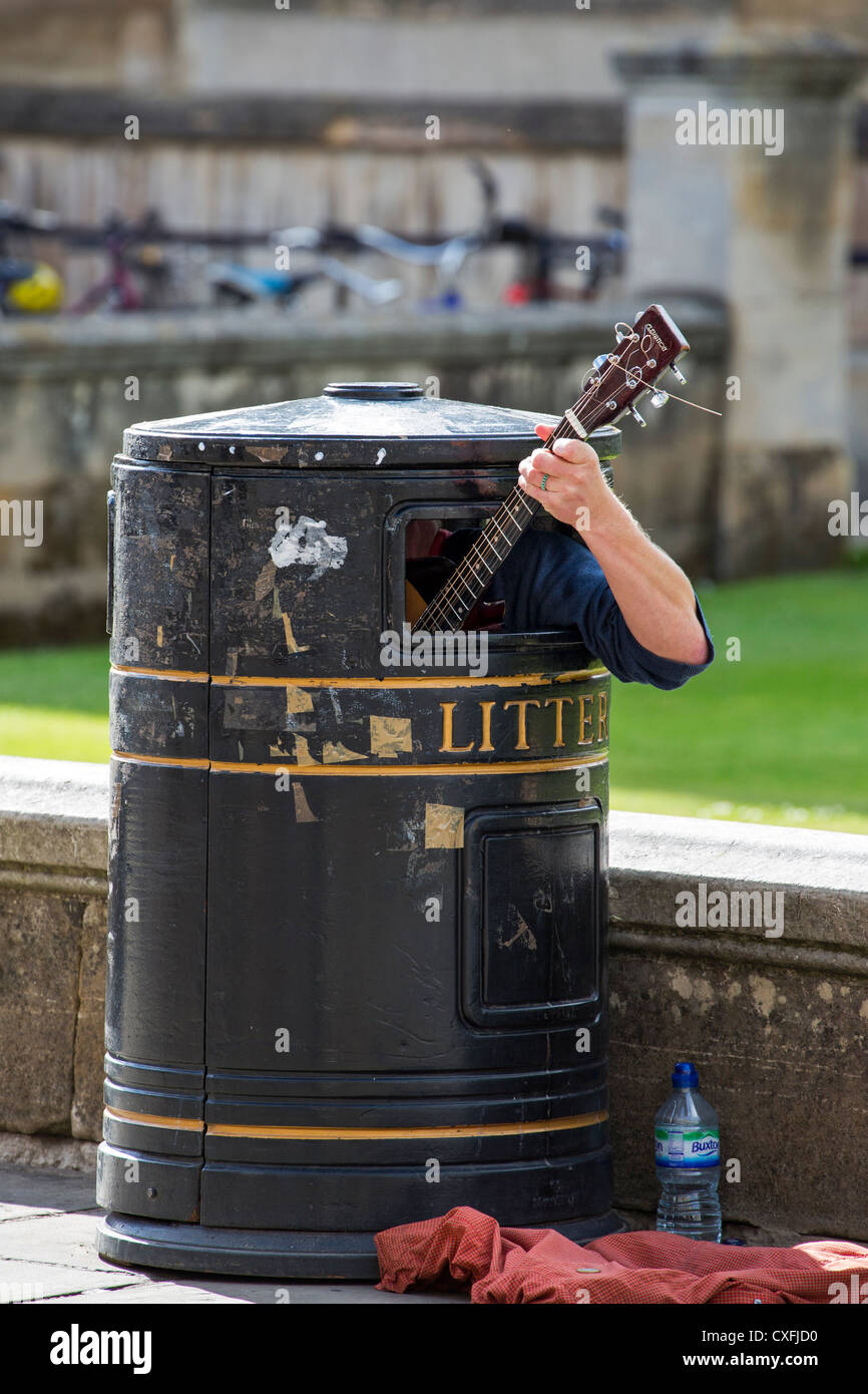 Guitarist in litter bin near King's College in Cambridge - Stock Image