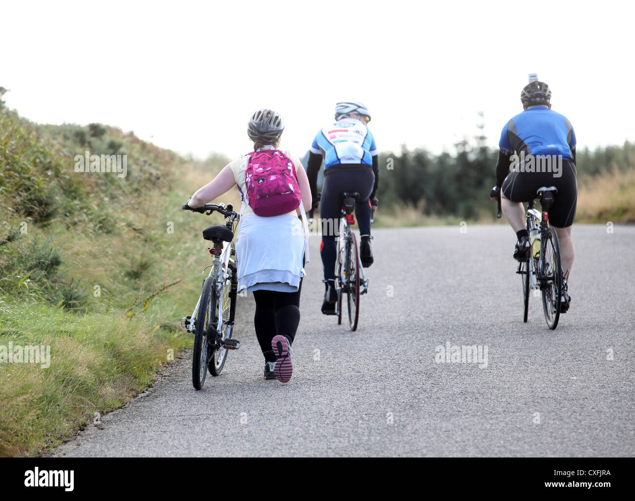 Female road cyclist pushing her bike up a hill in Aberdeenshire, Scotland, UK, as two men cycle past - Stock Image