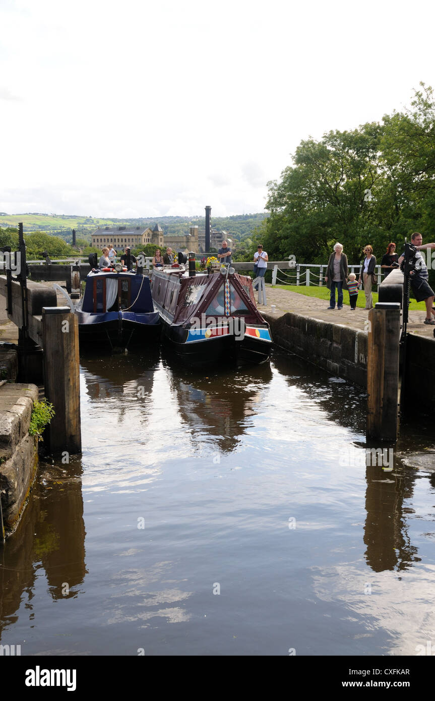 Two narrowboats exit the top chamber of Bingley Five-Rise Locks, on the Leeds and Liverpool Canal in Bingley, Yorkshire, - Stock Image