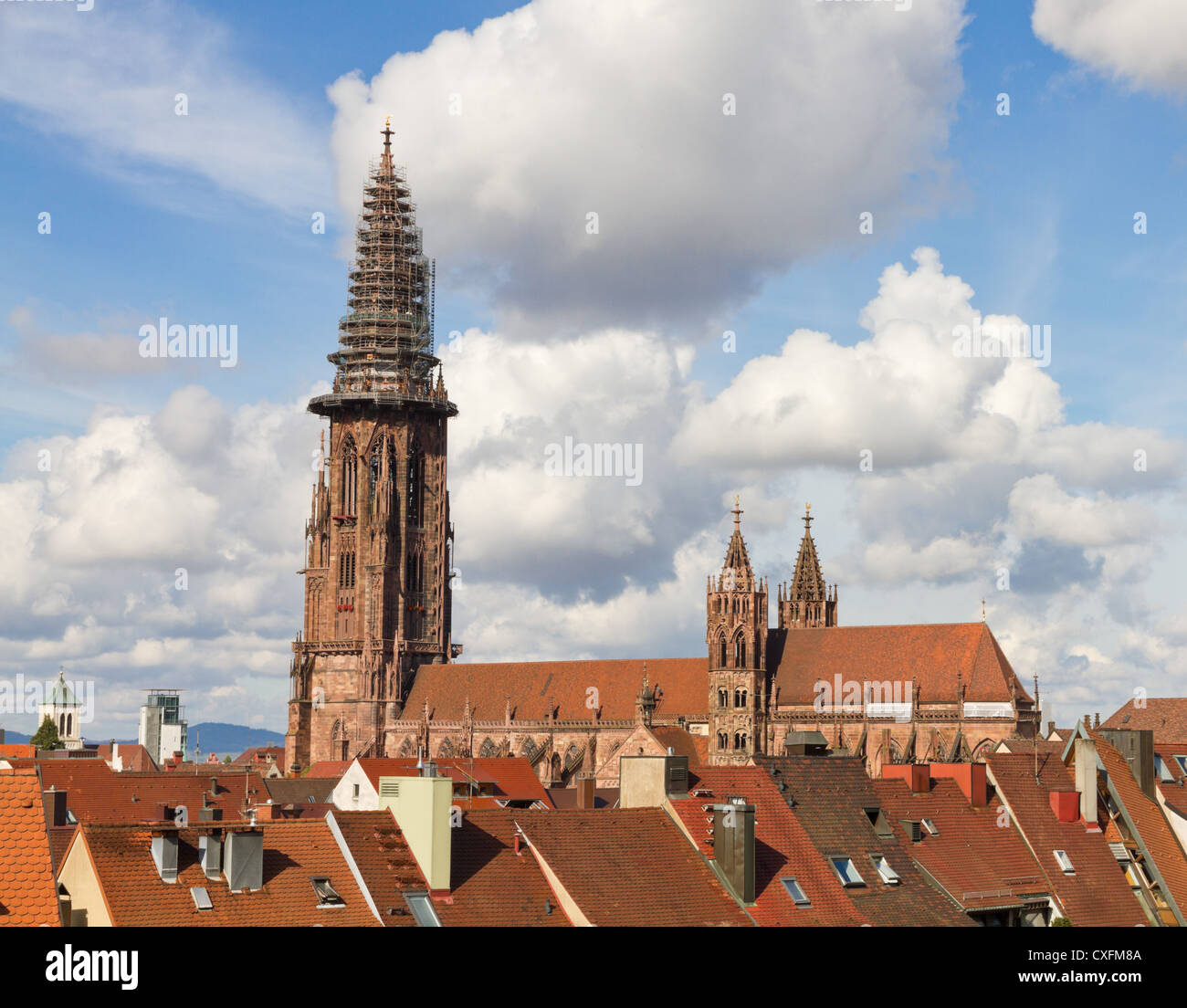 Old houses and minster with high tower of Gothic town, Freiburg im Breisgau minster Germany. - Stock Image