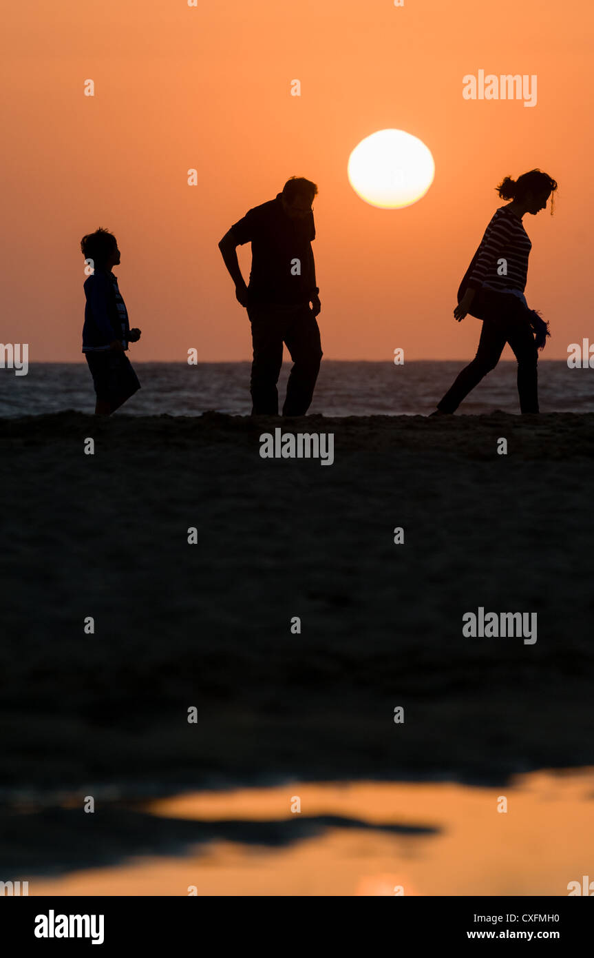 Family walking on the beach while admiring the sunset - Stock Image