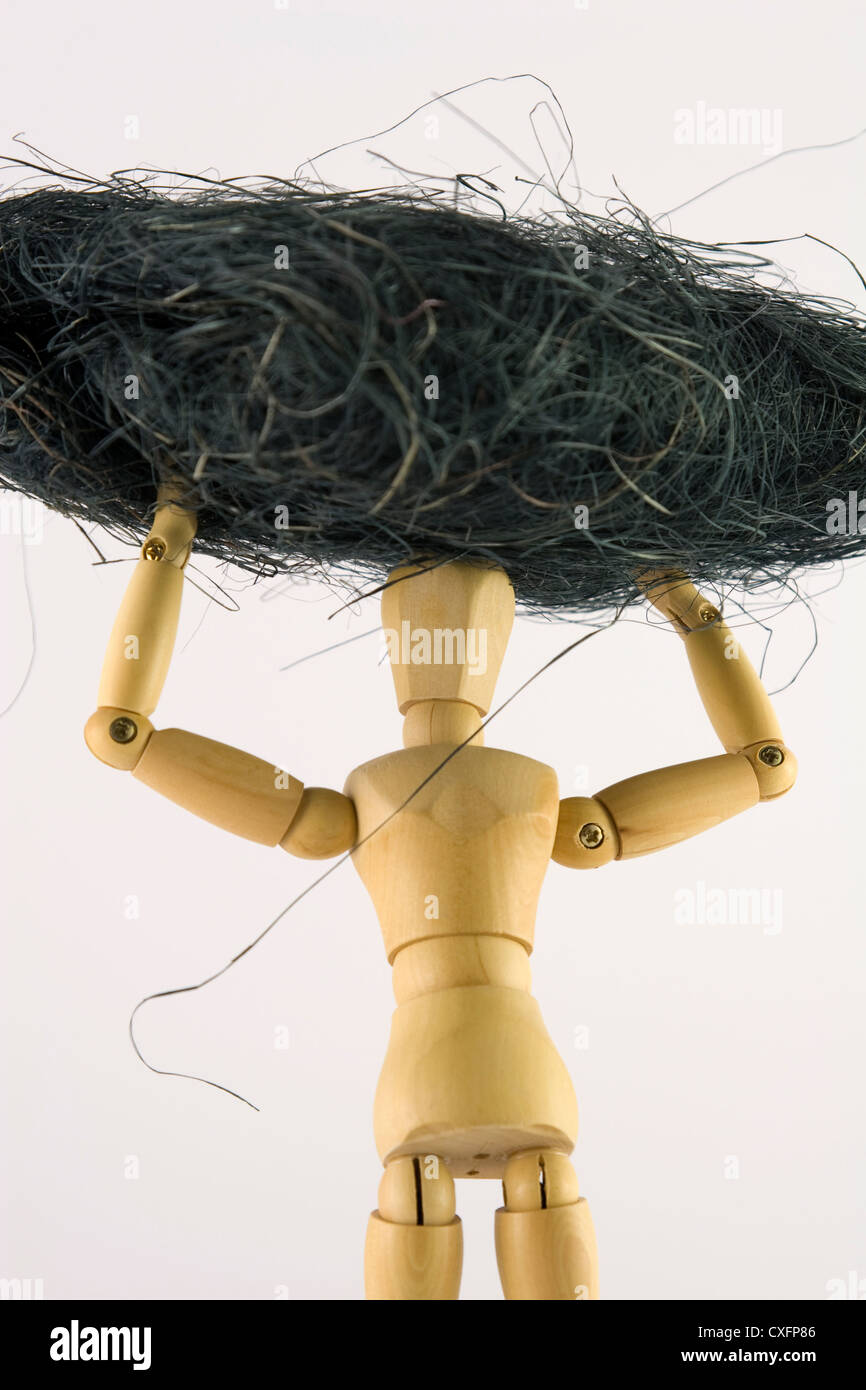 Human form holding a blackish cotton like bulk above its head. - Stock Image