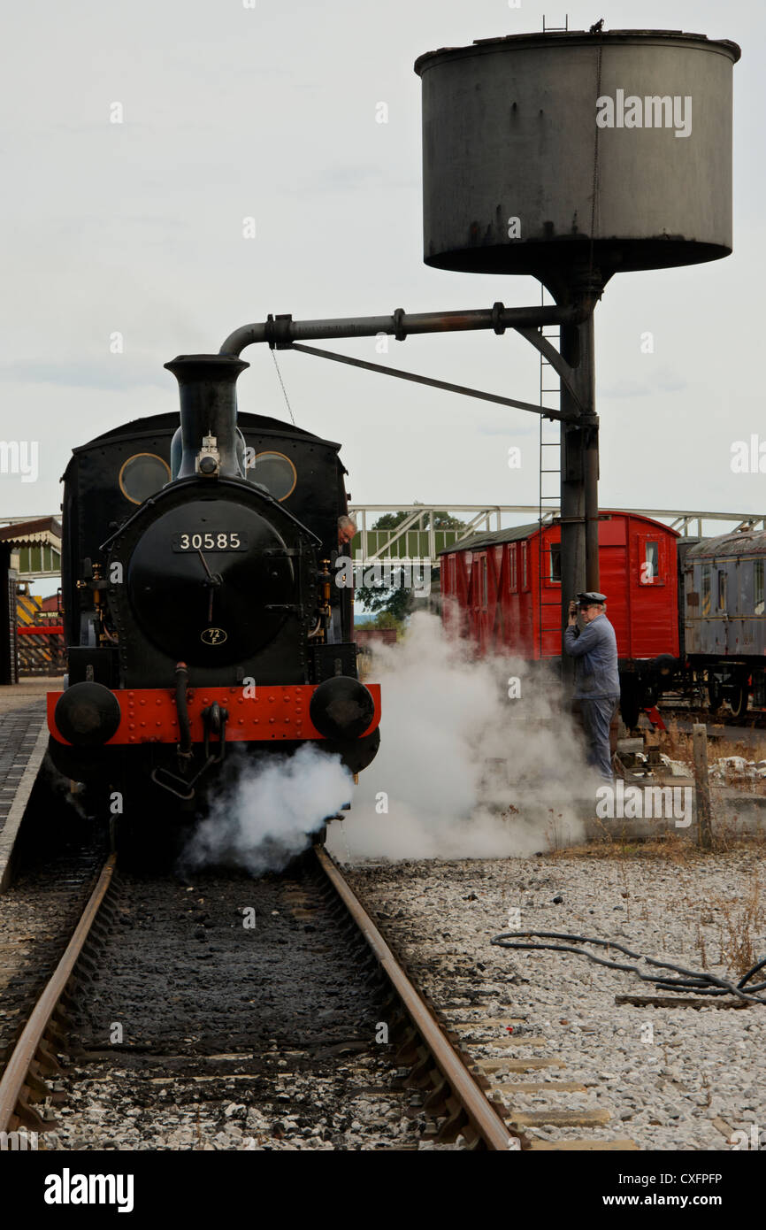Steam Locomotive at Buckinghamshire Railway Centre, Quainton, takes on water from the water crane - Stock Image