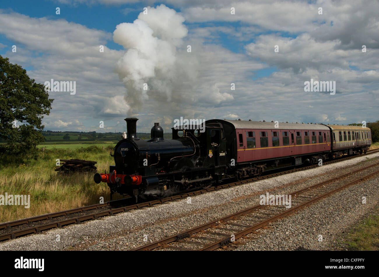 An old steam locomotive creates steam clouds that blend with the blue sky and clouds as it travels through the countryside. - Stock Image