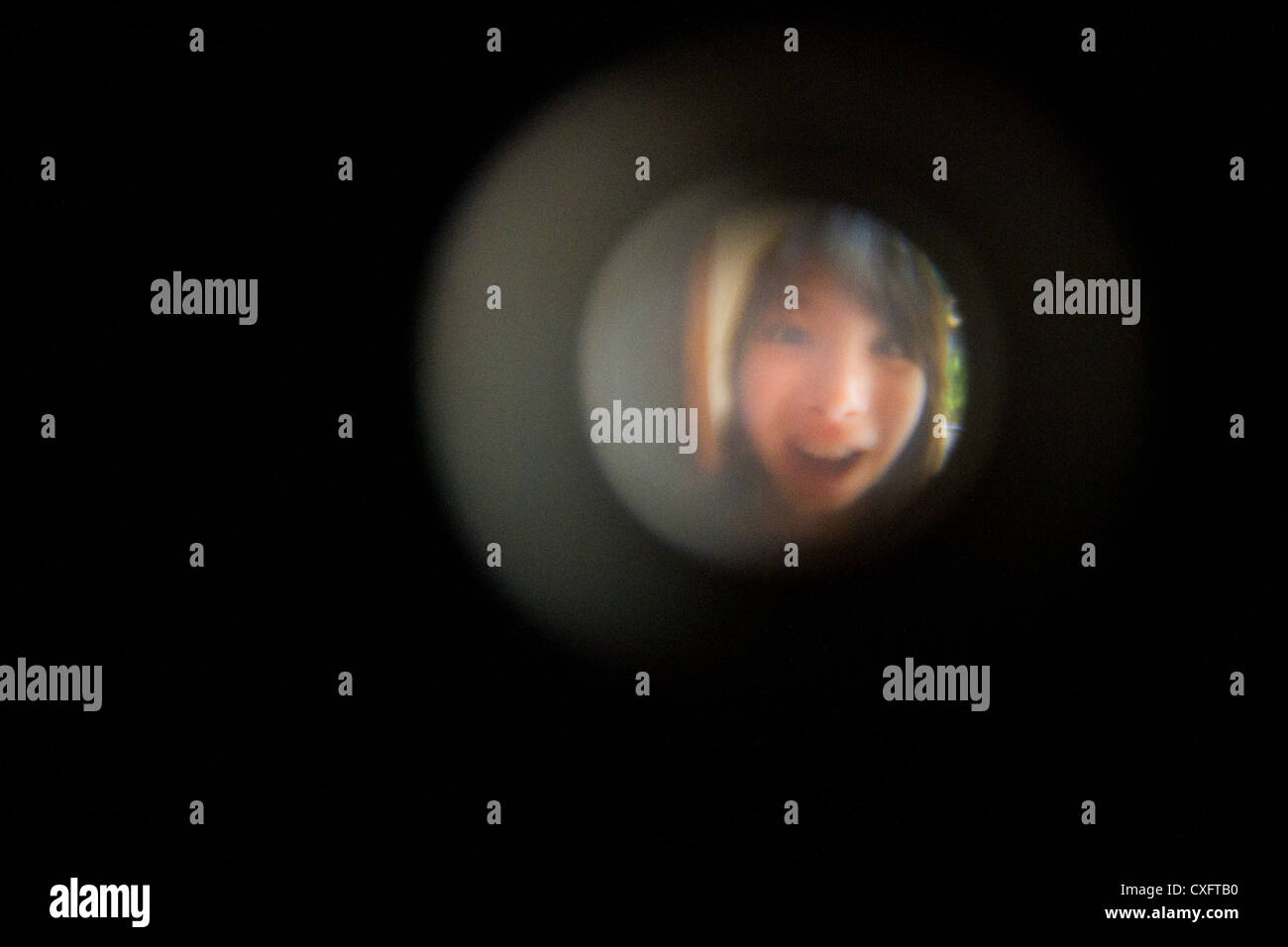 Girl beware the door looking on spy hole & Girl beware the door looking on spy hole Stock Photo: 50750196 - Alamy