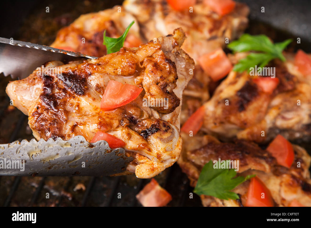 fry chicken piece with spice in tongs - Stock Image