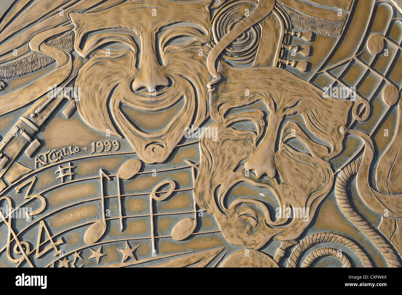 The faces of comedy and tragedy, symbol of drama, cast into the paving of a pedestrian street in Harrogate. - Stock Image