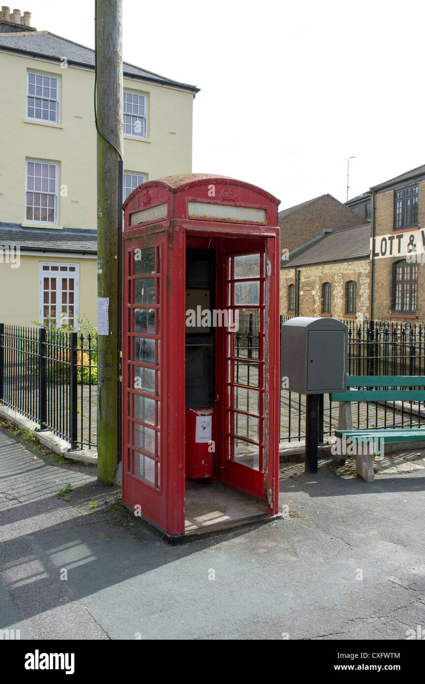 Vandalized public telephone kiosk or box with broken window and missing door - Stock Image
