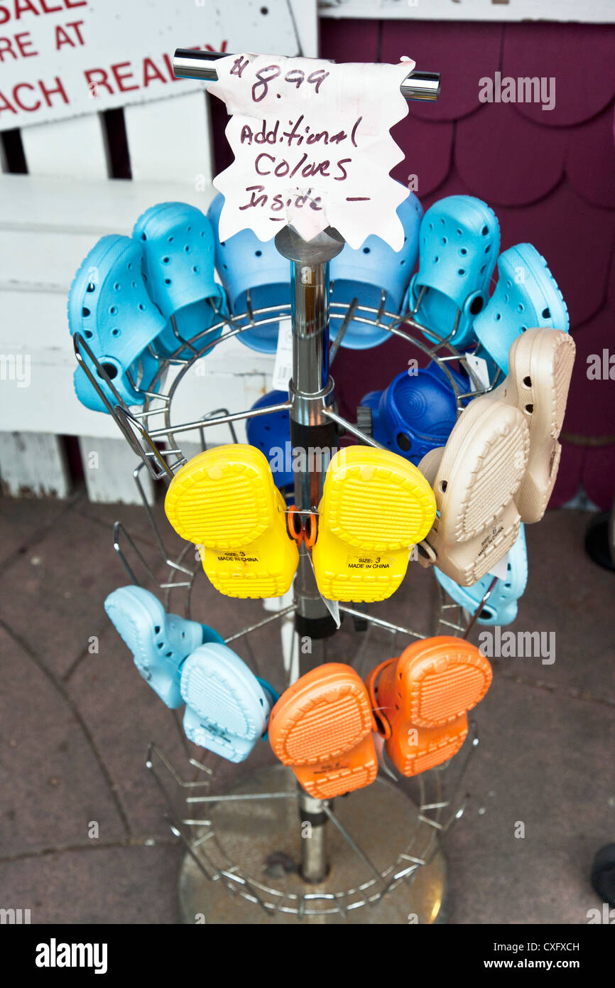 colorful croc shoes for little kids displayed on sidewalk rack outside shop on main street seaside town of Long - Stock Image