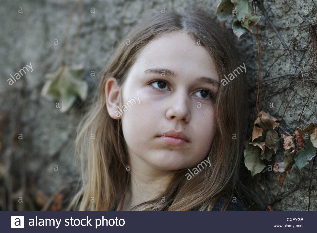 A close up of the face of a 13 year old girl leaning against a wall. - Stock Image