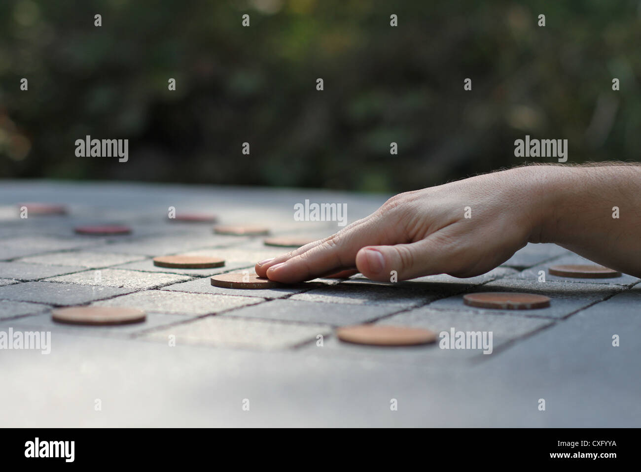A hand moving a checker piece on a large outdoor checker board. Stock Photo