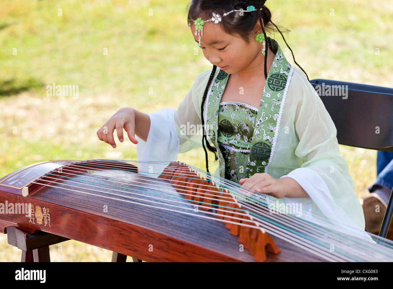 A young Chinese girl playing the guzheng (Chinese zither) - Stock Image