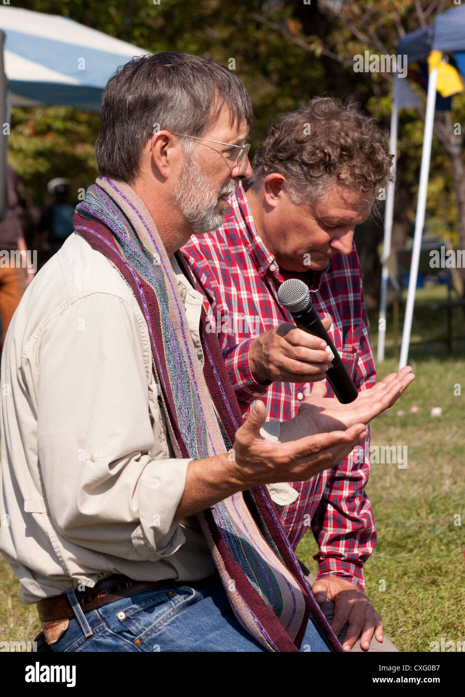 Man praying into a mic at an outdoor gathering - Stock Image