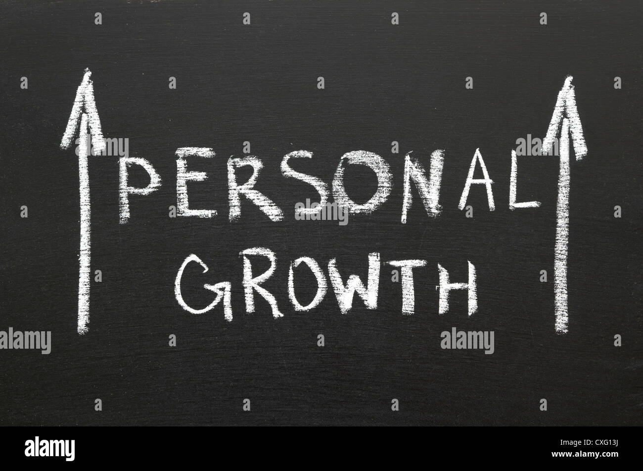 Personal growth phrase handwritten on the chalkboard with rising arrows - Stock Image
