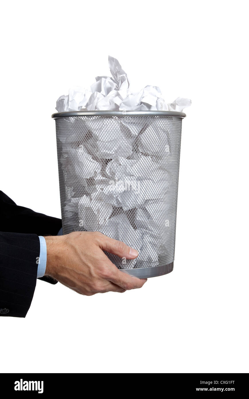 Business man's hand holding a wire trashcan full of paper - Stock Image