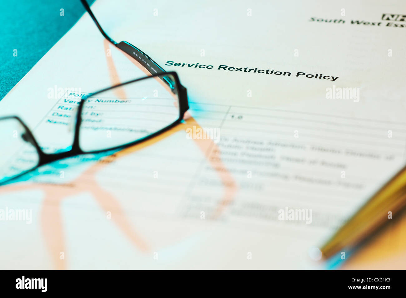 GP Glasses laying on a NHS service restriction policy document with atmospheric lighting and pen - Stock Image