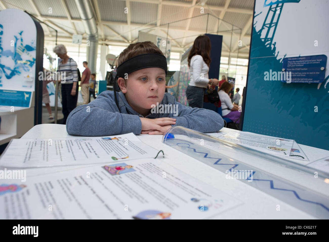Intech Science Centre child wearing headband to detect Alpha brainwaves during a mindball game sciences education Stock Photo