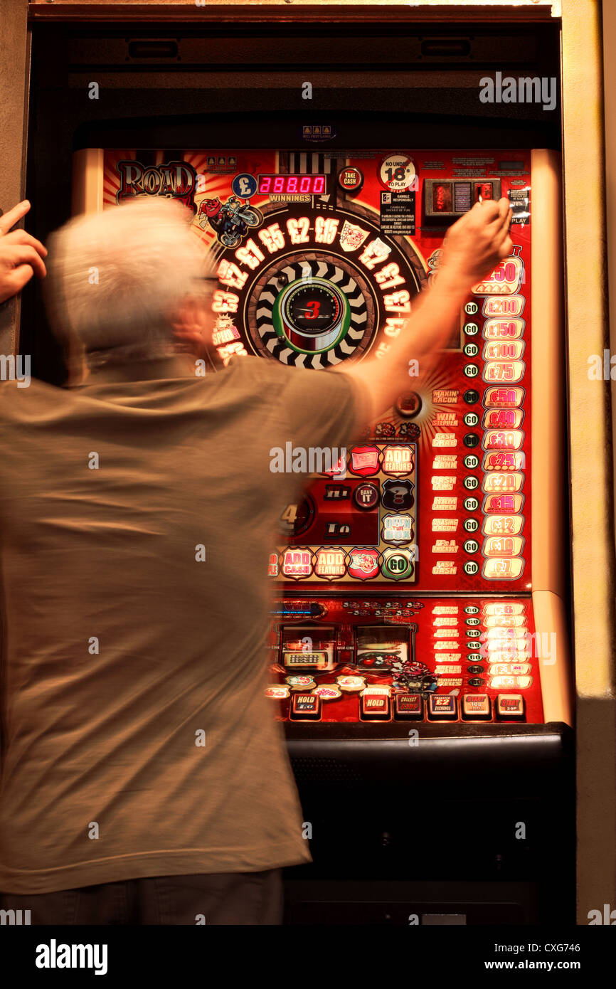 A man approximately 60 years old, (showing slight movement) placing a coin in a slot machine Stock Photo