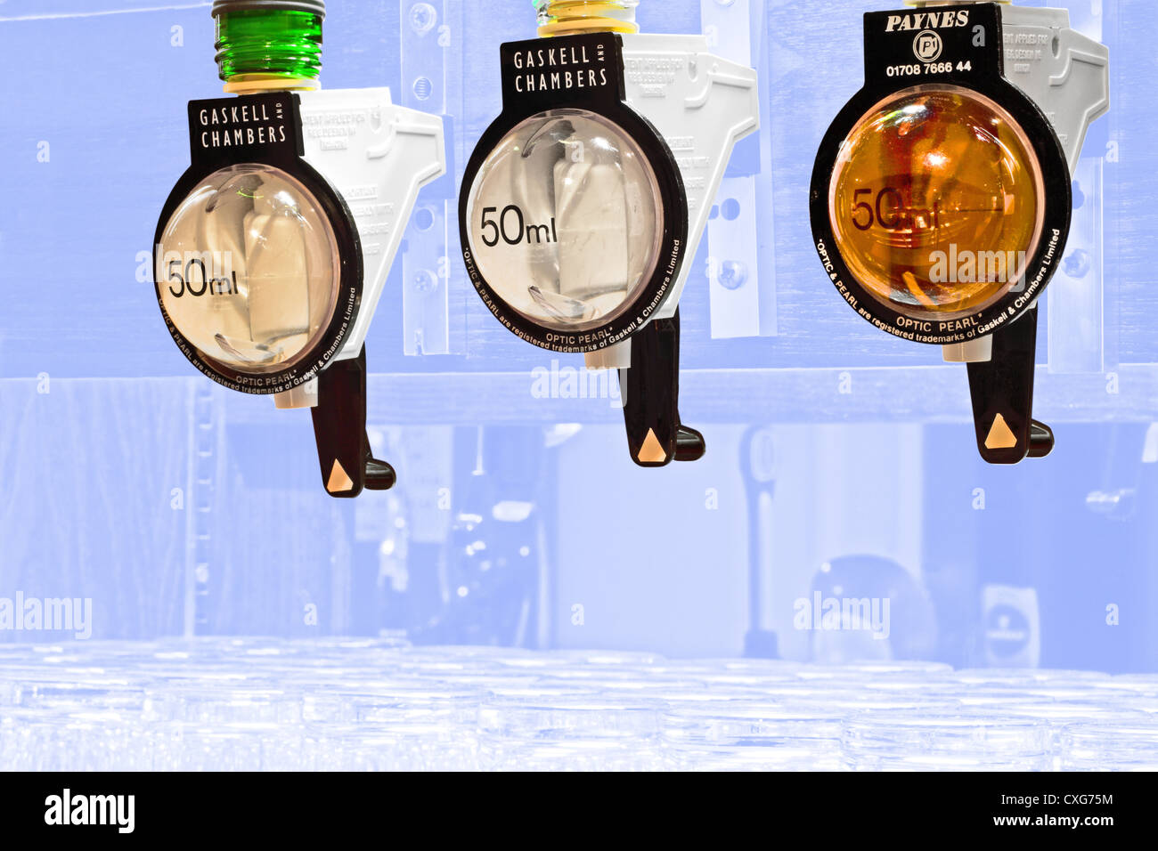 Three drinks optics showing a 50ml measure,with the background faded to a blue color so that the optics stand out - Stock Image