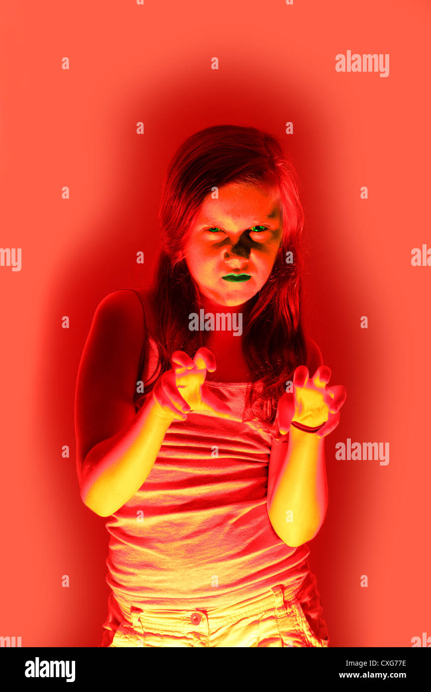 A ten year old girl with green lips and eyes looks menacing - Stock Image