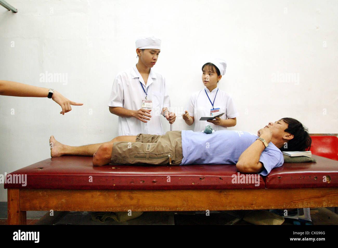 Students survey a leg amputee Orthopaedizentrum Saigon - Stock Image