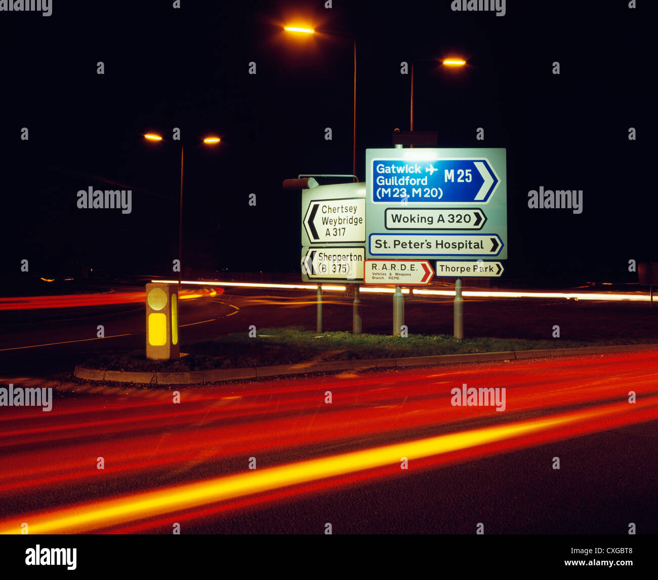 Road signs on roundabout above the M25 at Chertsey, Surrey, England. - Stock Image