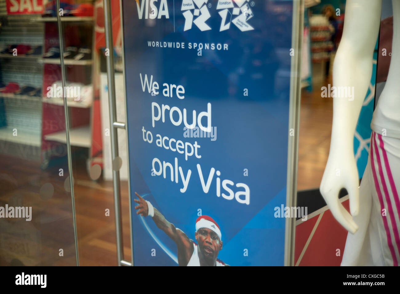 We are proud to accept only Visa sign in shop window selling 2012 London Olympic souvenirs - Stock Image