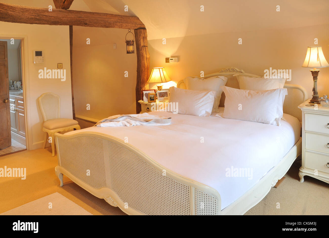 The interior designed bedroom of an english cottage with bed, bedside cabinets, lights, chairs and en suite bathroom. - Stock Image