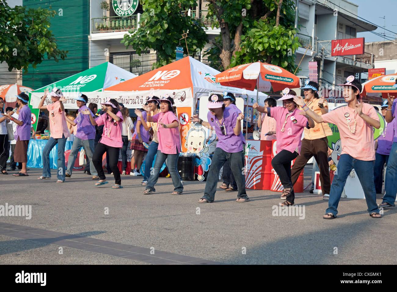 Dancing protestors (promoting reduced alcohol and cigarette consumption), Pratu Tha Phae, Chiang Mai, Thailand - Stock Image