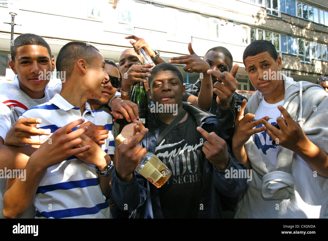 A lively group of young lads using gangsta gestures with hands and posing - Stock Image