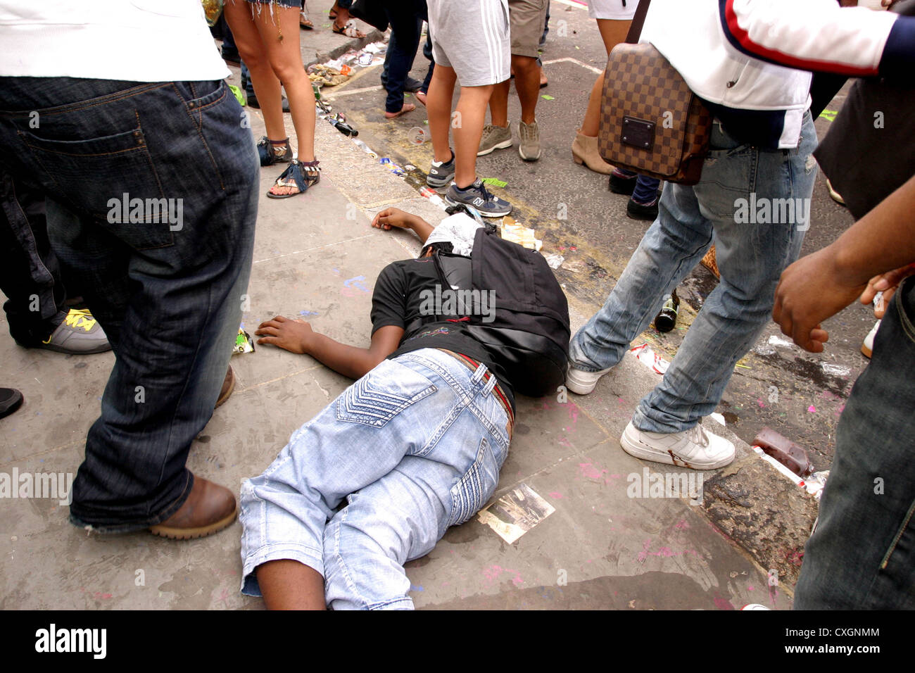 Youth collapsed in a crowded  street - Stock Image