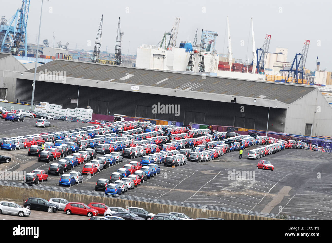 Newly imported multicoloured cars in car park at dock with cranes, warehouses and ship beyond - Stock Image