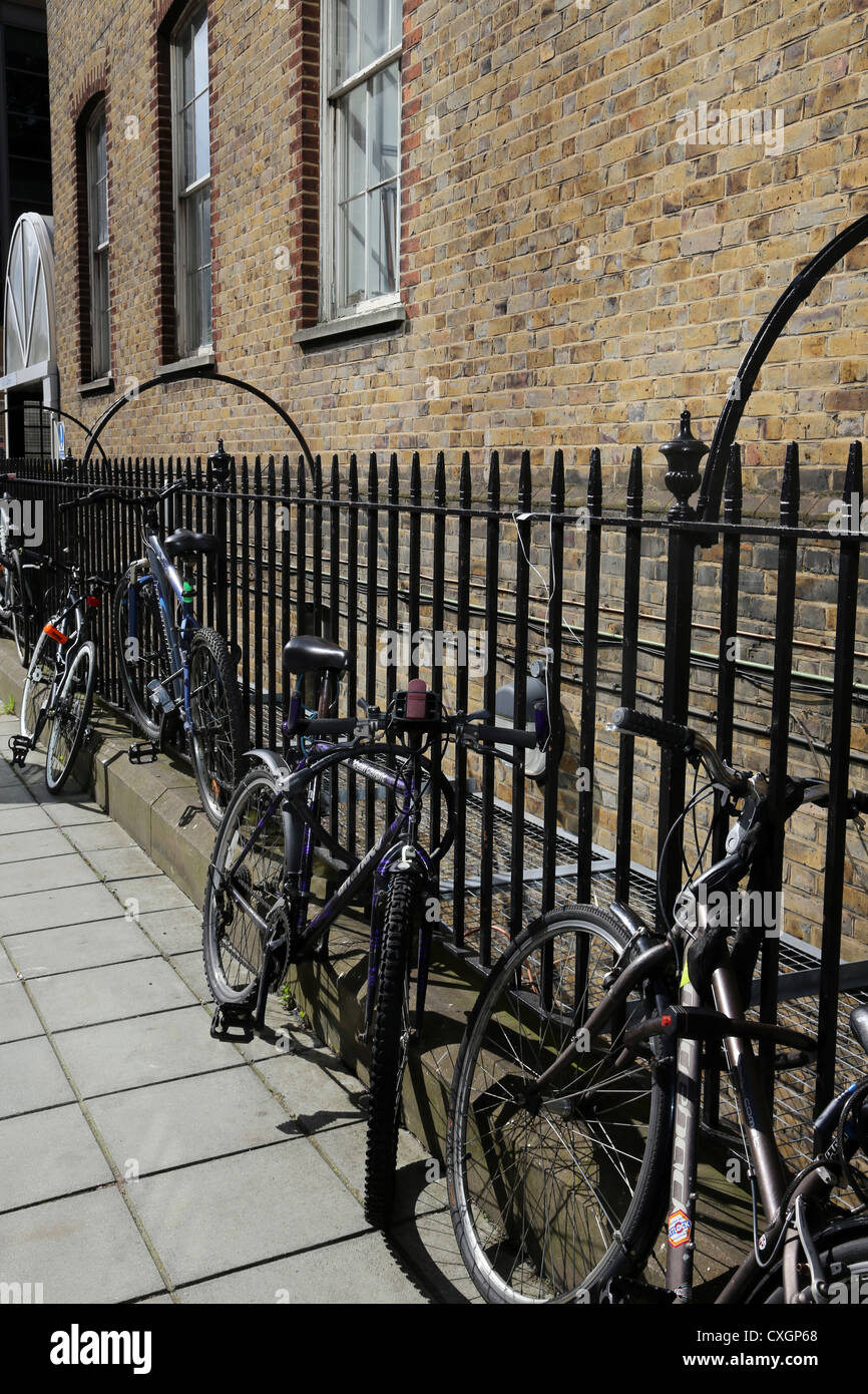 London England Bicycles Secured To Iron Railings - Stock Image