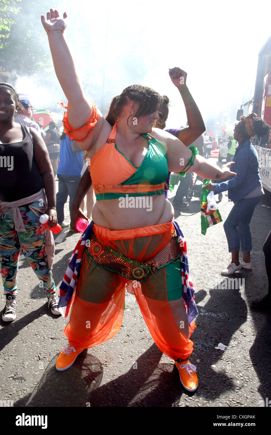 Overweight woman dancing at Notting Hill Carnival London - Stock Image