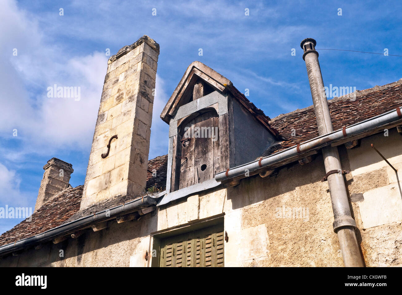 Village house gable, chimney and roof details - France. - Stock Image