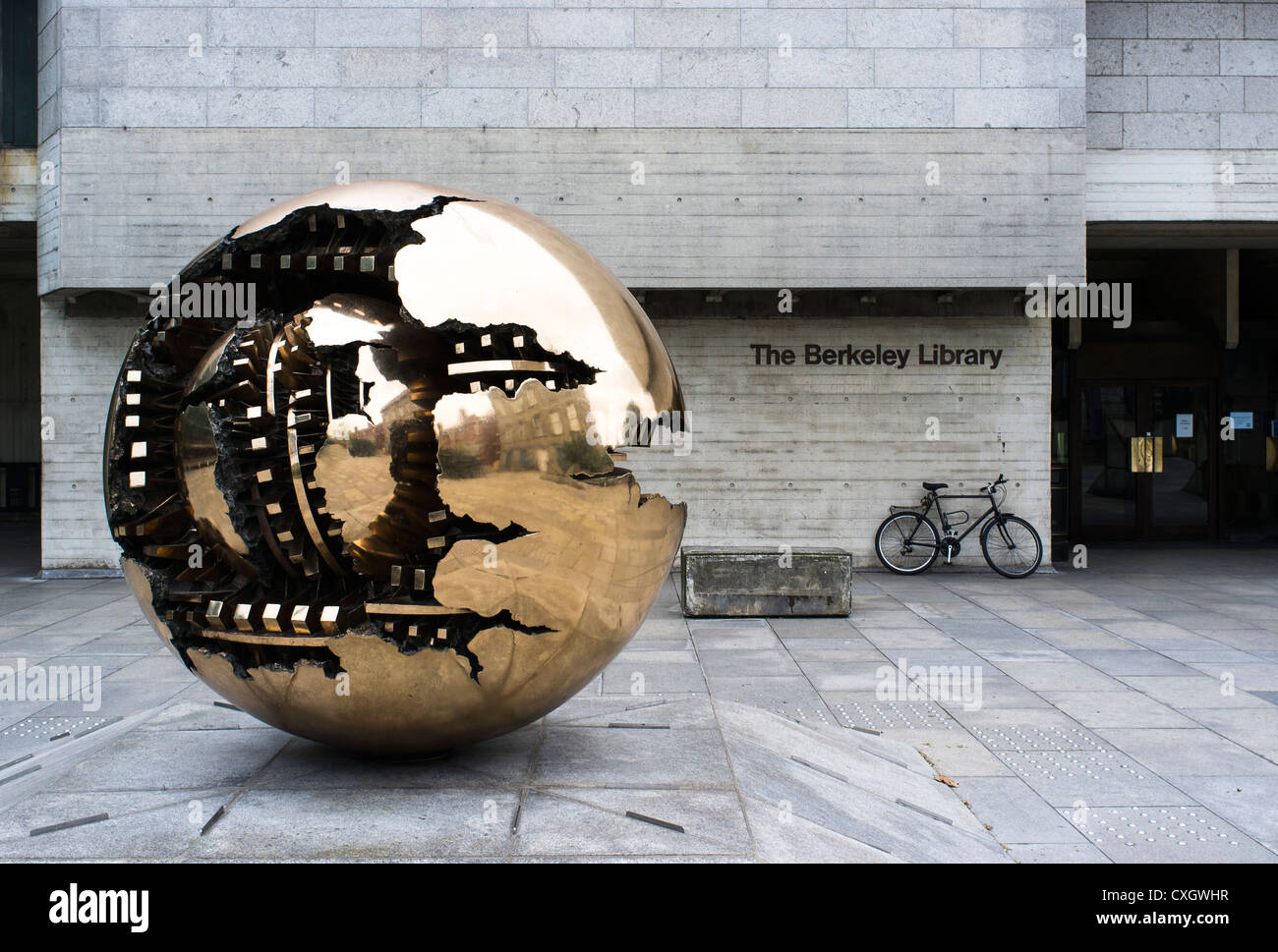 Sphere within a sphere by Arnaldo Pomodoro, Trinity College, Dublin, Ireland with The Berkeley Library in the background - Stock Image