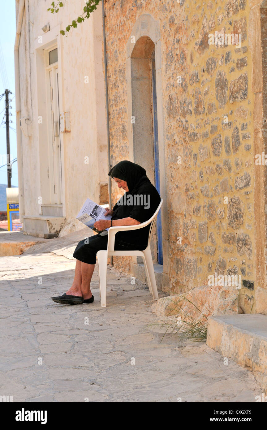 Old lady sitting outside her house in a shaded alleyway reading a newspaper, in the  hill top village of Pano Elounda, - Stock Image